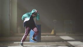Πεπειραμένος νέος χορευτής χιπ-χοπ που χορεύει κοντά στο βαρέλι σε ένα εγκαταλειμμένο κτήριο στην ομίχλη Πολιτισμός χιπ χοπ Πρόβα απόθεμα βίντεο