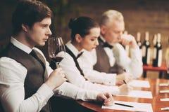 Πεπειραμένος πιό sommelier ερευνά το γούστο του κρασιού στο εστιατόριο Ο νέος σερβιτόρος δοκιμάζει τα οινοπνευματώδη ποτά στοκ εικόνες