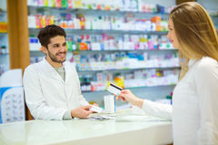 Πεπειραμένος φαρμακοποιός που συμβουλεύει το θηλυκό πελάτη στοκ φωτογραφίες