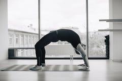 Πεπειραμένο να κάνει ατόμων γιόγκας διάφορο θέτει και τεντώνοντας ασκήσεις στο εσωτερικό, πανοραμική άποψη πόλεων στο υπόβαθρο Στοκ εικόνα με δικαίωμα ελεύθερης χρήσης