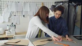 Πεπειραμένο seamstress διδάσκει το βοηθό της για να περιγράψει τα σχέδια ιματισμού στο ύφασμα Η νέα γυναίκα στρέφεται απόθεμα βίντεο
