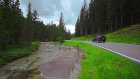 Περάσματα αυτοκινήτων στο δρόμο στη μέση των ξύλων με έναν ποταμό παράλληλα απόθεμα βίντεο