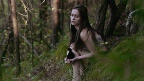 Περίεργα και συγκεντρωμένη νέα γυναίκα που φορούν τη γούνα η κορυφή κάθεται στο δασικό λόφο και τη σκέψη φιλμ μικρού μήκους