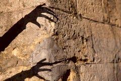 Περίεργα μαύρη σκιά σκιαγραφιών δύο χεριών σε έναν παλαιό καφετή τοίχο πετρών στοκ εικόνα