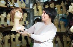 Περίεργη θηλυκή μοντέρνη περούκα brunette στο κατάστημα Στοκ Φωτογραφία