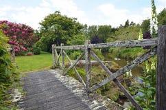 Περίεργη ξύλινη γέφυρα πέρα από τη λίμνη παπιών που οδηγεί στους όμορφους κήπους Στοκ Εικόνες