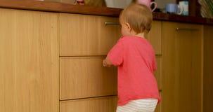 Περίεργη στάση παιδιών που κλίνει το συρτάρι κουζινών απόθεμα βίντεο