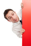 Περίεργος επιχειρηματίας πίσω από τον κόκκινο πίνακα διαφημίσεων Στοκ φωτογραφία με δικαίωμα ελεύθερης χρήσης