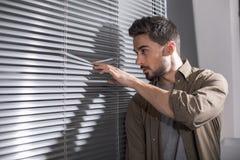 Περίεργος εργαζόμενος που κρυφοκοιτάζει μέσω του παραθύρου γραφείων στοκ εικόνα