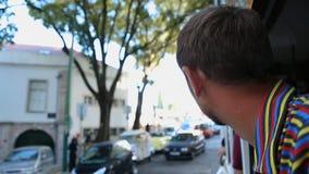 Περίεργος τουρίστας που κολλά το επικεφαλής έξω παράθυρό του και που βλέπει την περιβάλλουσα εικονική παράσταση πόλης απόθεμα βίντεο