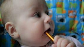Περίεργο αγόρι που κάθεται και που κρατά ένα χρωματισμένο ξύλινο κουτάλι στο στόμα του φιλμ μικρού μήκους