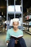 Περίεργο μαύρο βιβλίο ανάγνωσης σπουδαστών στη βιβλιοθήκη στοκ εικόνες