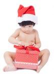 Περίεργο μωρό σε Santa ΚΑΠ που εξετάζει το giftbox Στοκ Φωτογραφία