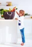 Περίεργο παιδί που βγαίνει φρούτα από το σύνολο τσαντών αγορών των τροφίμων στοκ εικόνα