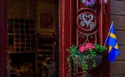 Περίκομψη κόκκινη πόρτα που διακοσμείται με μια σουηδική σημαία και ένα δοχείο ι λουλουδιών Στοκ εικόνα με δικαίωμα ελεύθερης χρήσης