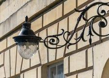 Περίκομψος λαμπτήρας επεξεργασμένου σιδήρου στο υποστήριγμα λαμπτήρων στην πρόσοψη ενός σπιτιού στο λουτρό στοκ εικόνες