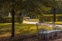 Περίκομψος πάγκος με τα πορτοκαλιά φύλλα στο πάρκο το φθινόπωρο στοκ εικόνα με δικαίωμα ελεύθερης χρήσης
