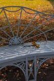 Περίκομψος πάγκος με τα πορτοκαλιά φύλλα στο πάρκο το φθινόπωρο στοκ εικόνες
