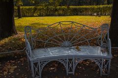 Περίκομψος πάγκος με τα πορτοκαλιά φύλλα στο πάρκο το φθινόπωρο στοκ εικόνα