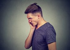 Περίλυπο λυπημένο άτομο στοχαστικό με την ανησυχημένη έκφραση προσώπου που κοιτάζει κάτω Στοκ Εικόνα