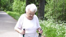 Περίπατοι γιαγιάδων με το σκανδιναβικό παλαιό γκρι ραβδιών περπατήματος απόθεμα βίντεο