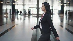 Περίπατοι επιχειρησιακών γυναικών γρήγορα μέσω του έξυπνου λόμπι ενός κτιρίου γραφείων απόθεμα βίντεο