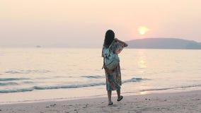 Περίπατοι κοριτσιών Toutist στην παραλία στο ηλιοβασίλεμα φιλμ μικρού μήκους