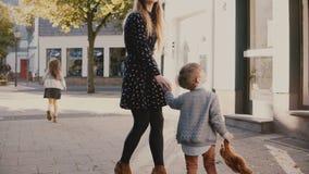 Περίπατοι μητέρων μαζί με το αγόρι και το κορίτσι κράτημα χεριών Η γυναίκα ξοδεύει το χρόνο με τα μικρά παιδιά οικογένεια τέσσερα απόθεμα βίντεο