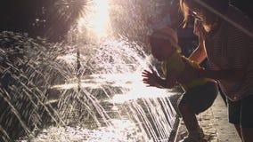 Περίπατοι μητέρων με το παιδί της στο πάρκο κοντά στην πηγή απόθεμα βίντεο