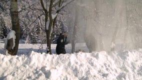 Περίπατοι νέοι οικογενειών μέσω του χιονισμένου δάσους βουνών στέκονται κάτω από ένα χιόνι δέντρων και κουνημάτων από ένα δέντρο  απόθεμα βίντεο