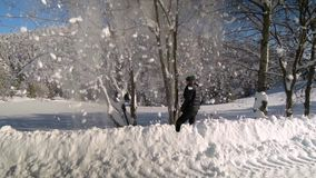 Περίπατοι νεαρών άνδρων μέσω ενός χιονώδους δάσους βουνών τινάζει το χιόνι από ένα δέντρο Είναι ευτυχής και διασκέδαση γέλιου κίν απόθεμα βίντεο