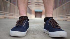 Περίπατοι νεαρών άνδρων προς τη κάμερα που φορά τα μπλε παπούτσια απόθεμα βίντεο
