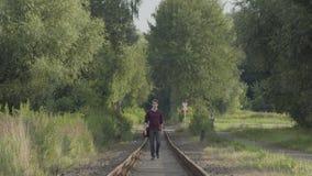 Περίπατοι νεαρών άνδρων στις παλαιές διαδρομές τραίνων φιλμ μικρού μήκους