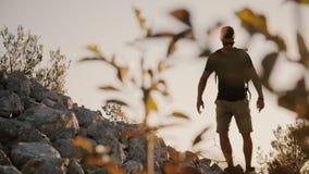 Περίπατοι οδοιπόρων κατά μήκος του στενού λόφου κορυφογραμμών συνόδου κορυφής στο ηλιοβασίλεμα επίτευξη της κορυφής Νεαρός άνδρας απόθεμα βίντεο