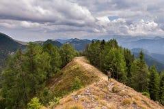 Περίπατοι οδοιπόρων στην κορυφογραμμή βουνών κάτω από έναν θυελλώδη ουρανό στοκ εικόνα
