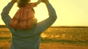 Περίπατοι πατέρων με την κόρη του στους ώμους του στις ακτίνες του ηλιοβασιλέματος Ο μπαμπάς συνεχίζει τους ώμους του αγαπημένου  φιλμ μικρού μήκους