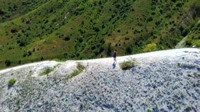 Περίπατοι τουριστών κοριτσιών στα βουνά Το κορίτσι πάνω από το λόφο εξετάζει τον ποταμό απόθεμα βίντεο