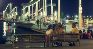Περίπατοι τουριστών στη γέφυρα πέρα από τη μαρίνα Vell λιμένων τη νύχτα bridge illuminated απόθεμα βίντεο