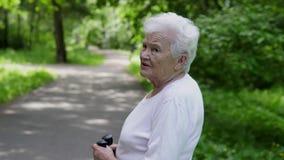 Περίπατοι Grandma στο πάρκο με τα ραβδιά για το σκανδιναβικό περπάτημα απόθεμα βίντεο