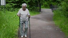 Περίπατοι Grandma στο πάρκο με τα ραβδιά για το σκανδιναβικό περπάτημα στην αποχώρηση απόθεμα βίντεο