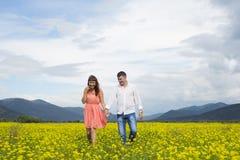 Περίπατος ανδρών και γυναικών εραστών στον τομέα λουλουδιών Στοκ φωτογραφίες με δικαίωμα ελεύθερης χρήσης