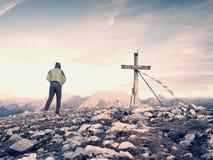 Περίπατος ατόμων κατά μήκος του ξύλινου σταυρού σε μια αιχμή βουνών που χτίζεται στις Άλπεις victiims Σταυρός στην κορυφή Στοκ Εικόνα