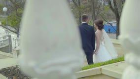 Περίπατος γαμήλιων ζευγών κάτω στα σκαλοπάτια και τα χέρια εκμετάλλευσης backview απόθεμα βίντεο