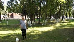 Περίπατος γυναικών με το σκυλί στο πάρκο κορίτσι έγκυο έγκυος γυναίκα πάρκων απόθεμα βίντεο