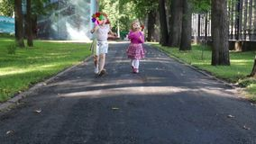 Περίπατος δύο ευτυχής μικρών κοριτσιών με τους ανεμόμυλους στο πάρκο απόθεμα βίντεο