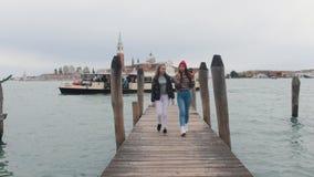 Περίπατος δύο νέος γυναικών κατά μήκος της αποβάθρας άμεσα στη κάμερα Να περπατήσει δίπλα-δίπλα απόθεμα βίντεο