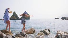 Περίπατος δύο όμορφος γυναικών πέρα από τις πέτρες στη θάλασσα σε Σορέντο φιλμ μικρού μήκους