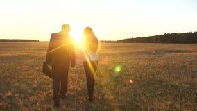 Περίπατος επιχειρηματιών και επιχειρηματιών πέρα από τον τομέα στις ακτίνες του ηλιοβασιλέματος απόθεμα βίντεο