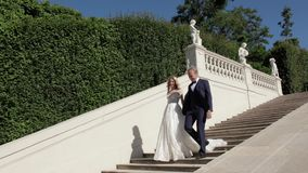 Περίπατος ζεύγους κοντά στο μεγάλο παλάτι Κομψοί νεόνυμφος και νύφη στα γαμήλια ενδύματά τους Αγάπη απόθεμα βίντεο