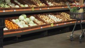 Περίπατος ζεύγους με το καροτσάκι κοντά στην επίδειξη με τα λαχανικά απόθεμα βίντεο